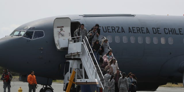 Relatives of passengers of a missing military plane arrive in a Chilean military airplane to an airbase in Punta Arenas, Chile, Wednesday, Dec. 11, 2019. (AP Photo/Fernando Llano)