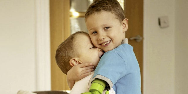 Jacob Scrimshaw, 5, hugging his younger brother Sebastian, 3 with his new prosthetic arm.