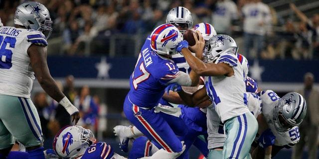 Buffalo Bills quarterback Josh Allen (17) fights for a initial down after recuperating a fumbled snap as Dallas Cowboys cornerback Byron Jones (31) defends in a initial half of an NFL football diversion in Arlington, Texas, Thursday, Nov. 28, 2019.