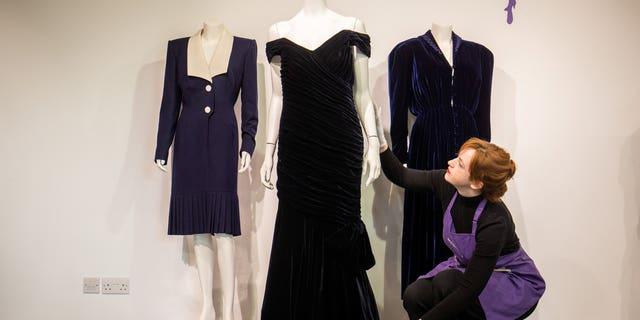An assistant adjusts Princess Diana's iconic 'Travolta Dress' at Kerry Taylor Auctions.