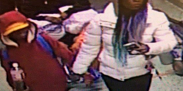 In this image taken from surveillance video released by the Atlanta Police Department, a woman escorts a young man into Grady Memorial Hospital in Atlanta on the night of Dec. 4. Police later identified the woman as Diana Elliott, and arrested her.