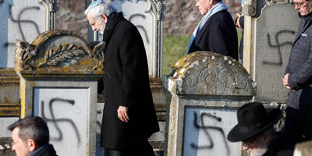 Members of the Jewish community walk amid vandalized tombs in the Jewish cemetery of Westhoffen, west of the city of Strasbourg, on Wednesday. (AP)