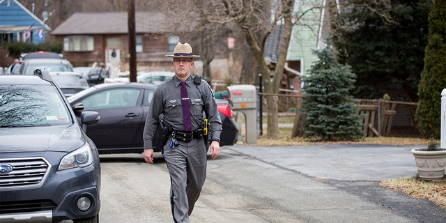 A New York state trooper walking past the house, with green siding, of the mother of Grafton Thomas, the primary suspect in the Saturday night stabbings at a rabbi's home in Monsey, N.Y. (AP)