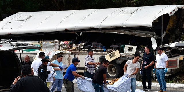 Rescue workers carry body bags with the remains of passengers after a deadly bus accident in Gualan, Guatemala, Saturday, Dec. 21, 2019. The accident killed at least 21 people and left a dozen wounded, according to the national disaster agency. (Associated Press)
