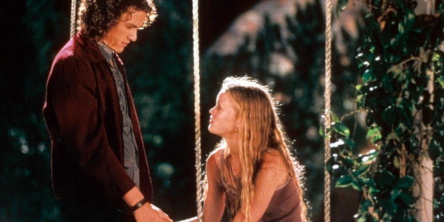 Heath Ledger and Julia Stiles at swing in a scene from the film '10 Things I Hate About You', 1999.