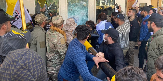 Protesters smash a window inside the U.S. embassy compound in Baghdad on Tuesday. [AP)