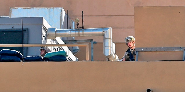 U.S. soldiers stand guard on the roof of the U.S. embassy in Baghdad, Iraq, on Tuesday. (AP)