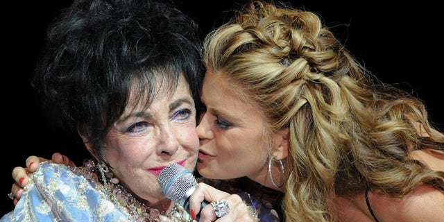 Model Kathy Ireland kisses Elizabeth Taylor during the 27th Annual Macy's Passport Fashion Show Benefit at Barker Hanger on September 24, 2009 in Santa Monica, California.