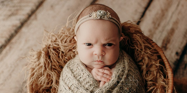 """Justine Tuhy, who photographed the session, described the little grump as """"the best baby facial expressions I have ever captured!"""""""