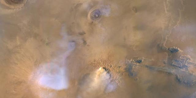 "The yellow-white cloud at the bottom center of this image is a ""dust tower"" on Mars, as seen by NASA's Mars Reconnaissance Orbiter on Nov. 30, 2010."