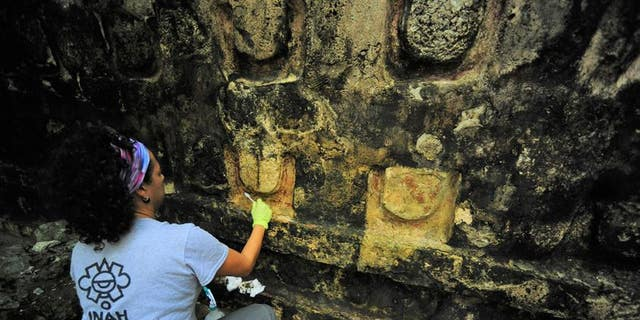 An archaeologist cleans a portion of the building found in Kuluba.