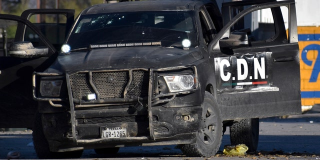 A damaged pick up marked with the initials C.D.N., that in Spanish stand for Cartel of the Northeast, is on the streets after a gun battle between Mexican security forces and suspected cartel gunmen, in Villa Union, Mexico, Saturday, Nov. 30, 2019.