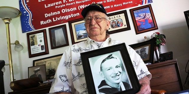 ​​​​​​​Lauren Bruner, a survivor of the USS Arizona which was attacked on Dec. 7, 1941, holds with a 1940 photo of himself at his home in La Mirada, Calif., Nov. 17, 2016. He died earlier in 2019 at age 98. (Associated Press)