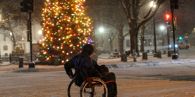 Stephen Willard pushes his wheelchair through the snow as he heads to his apartment in Keene, N.H., Sunday, Dec. 1, 2019.