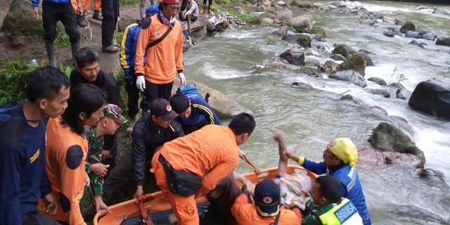 In this photo released by the National Search And Rescue Agency (BASARNAS), rescuers remove the body of a victim of a bus accident in Pagaralam, Indonesia, Tuesday, Dec. 24, 2019. A number of people were killed when the passenger bus plunged into the ravine on Sumatra island after its brakes apparently malfunctioned, police said Tuesday. (BASARNAS via AP)