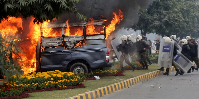 The angry lawyers set police vehicles on fire during the clashes in Lahore. (AP Photo/K.M. Chaudary)