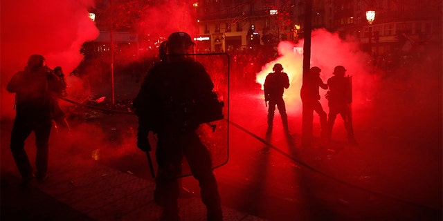 Riot police officers secure an area as some demonstrators were seen smashing store windows, setting fires and hurling flares in eastern Paris Thursday. (AP)