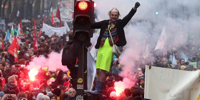 A man stands on a traffic light during a demonstration in Paris on Thursday. (AP)