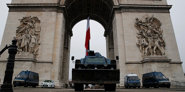 Police vehicles park by the Arc de Triomphe in Paris on Thursday.