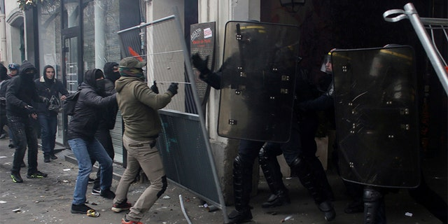 Youth clash with riot police officers during a demonstration in Paris on Thursday. (AP)