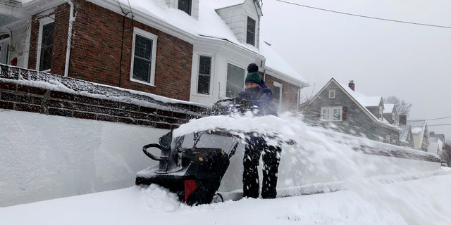 Doreen Goy, of Warwick, R.I., uses a snowblower to clear a sidewalk after a second round of snow struck the area, on Tuesday. Hospitals in Massachusetts reported a rash of snowblower-related hand injuries over a two-day period