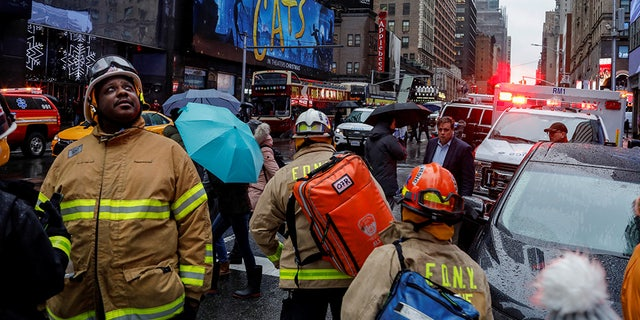 Fire Department of New York (FDNY) personnel and New York Police Department (NYPD) officers work at the scene as a woman was reported dead after debris fell on her near Times Square