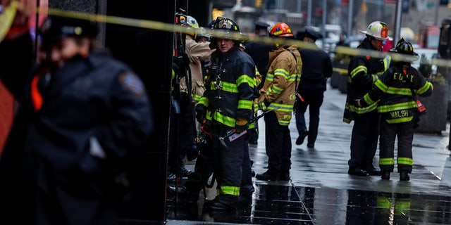 Fire Department of New York (FDNY) personnel and New York Police Department (NYPD) officers work at the scene as a woman was reported dead after debris fell on her near Times Square in Manhattan, New York, U.S., December 17, 2019.