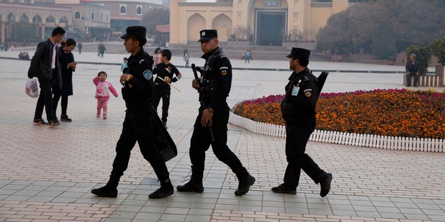 Uighur security personnel patrol near the Id Kah Mosque in Kashgar in western China's Xinjiang region. Classified documents, leaked to a consortium of news organizations, lay out the Chinese government's deliberate strategy to lock up ethnic minorities to rewire their thoughts and even the language they speak. (AP Photo/File)