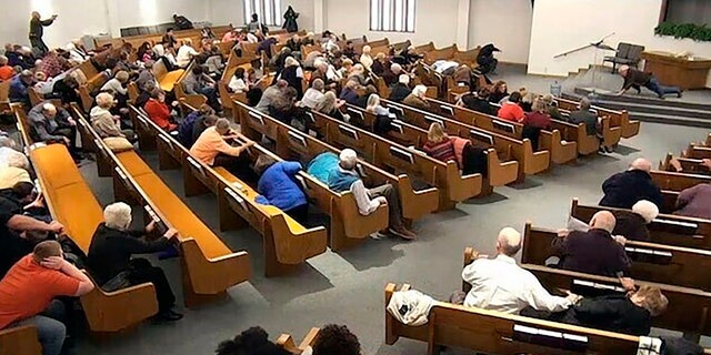 In this still frame from livestreamed video provided by law enforcement, churchgoers take cover while a congregant armed with a handgun, top left, engages a man who opened fire, near top center just right of windows, during a service at West Freeway Church of Christ, Sunday, Dec. 29, 2019, in White Settlement, Texas.