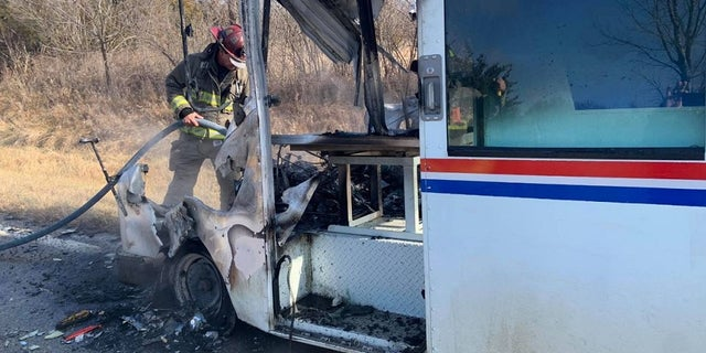 An Osawatomie firefighter extinguishes a mail truck fire Sunday.