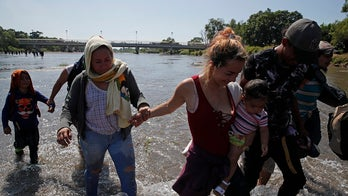 Caravan migrants cross Mexico river, throw rocks at country's national guard in response to tear gas