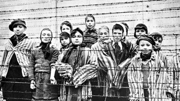 A group of child survivors behind a barbed-wire fence at the Nazi concentration camp at Auschwitz-Birkenau, on the day of the camp's liberation by the Red Army, 27th January 1945. The photo was taken by Red Army photographer Captain Alexander Vorontsov.