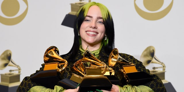 "Billie Eilish poses in the press room with the awards for best album and best pop vocal album for ""We All Fall Asleep, Where Do We Go?"", best song and record for ""Bad Guy"" and best new artist at the 62nd annual Grammy Awards at the Staples Center on Sunday, Jan. 26, 2020, in Los Angeles."