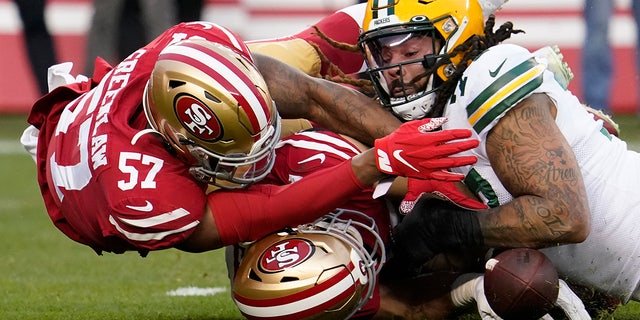 Green Bay Packers offensive lineman Billy Turner, right, recovering a loose ball next to San Francisco 49ers linebacker Dre Greenlaw (57) and defensive end Nick Bosa during Sunday's game. (AP Photo/Tony Avelar)