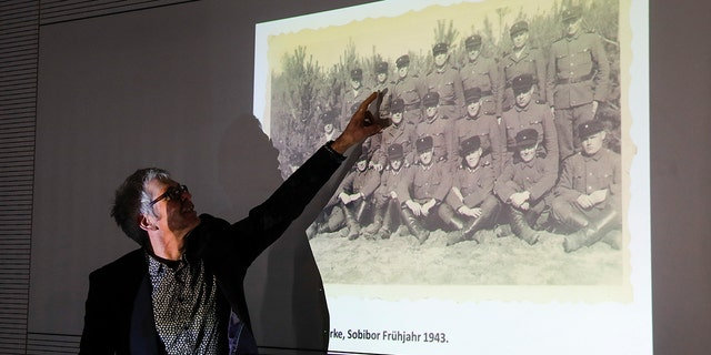 Historican Martin Cueppers points at a man, presumably former security guard John Demjanjuk, at the Nazi death camp Sobibor during a news conference of newly discovered photos from the Sobibor camp in Berlin, Germany, Tuesday, Jan. 28, 2020. (AP Photo/Markus Schreiber)