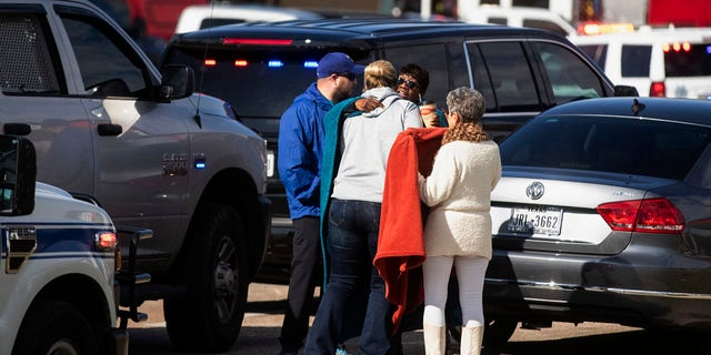 Residents embrace near police and fire cars that surround the scene of a shooting at West Freeway Church of Christ in White Settlement, Texas, Sunday, Dec. 29, 2019. (Yffy Yossifor/Star-Telegram via AP)
