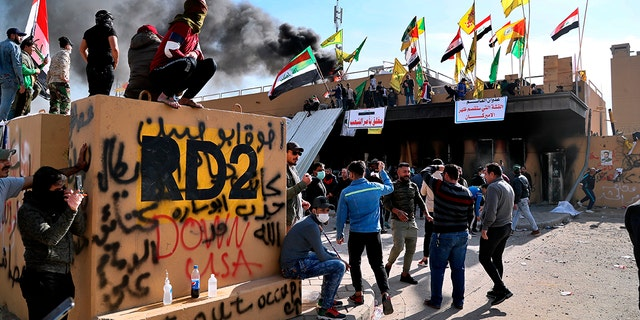 Pro-Iranian militiamen and their supporters set a fire during a sit-in in front of the U.S. embassy in Baghdad, Iraq, Wednesday, Jan. 1, 2020. (AP Photo/Khalid Mohammed)