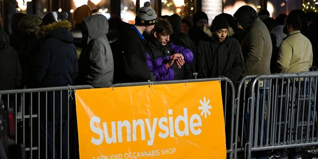 A long line of people brave the cold as they wait to be the first in Illinois to purchase recreational marijuana at Sunnyside dispensary Wednesday, Jan. 1, 2020, in Chicago. (AP Photo/Paul Beaty)