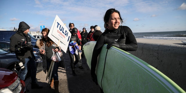 Democratic presidential candidate U.S. Rep. Tulsi Gabbard, D-Hawaii, carries her surfboard after surfing the Atlantic Ocean, Wednesday, Jan. 1, 2020, in Hampton, N.H. (AP Photo/Cheryl Senter)