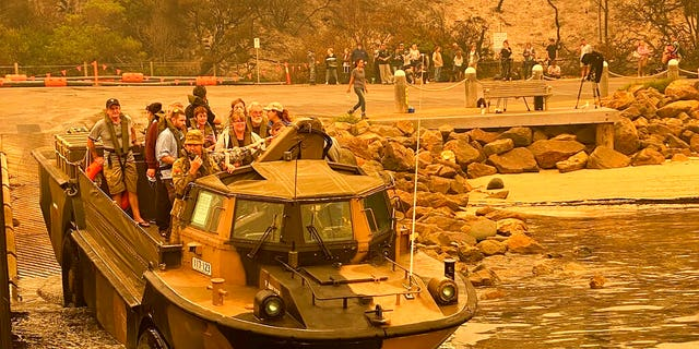 Evacuees are transported in a lighter, amphibious, resupply, cargo (LARC) amphibious vehicle, from Mallacoota, Victoria, on Jan. 2, 2020. Navy ships plucked hundreds of people from beaches and tens of thousands were urged to flee before hot weather and strong winds in the forecast worsen Australia's already devastating wildfires.