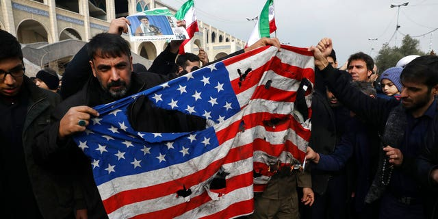 "Protesters burn a U.S. flag during a demonstration over the U.S. airstrike in Iraq that killed Iranian Revolutionary Guard Gen. Qassem Soleimani, in Tehran, Iran, Jan. 3, 2020. Iran has vowed ""harsh retaliation"" for the U.S. airstrike near Baghdad's airport that killed Tehran's top general and the architect of its interventions across the Middle East, as tensions soared in the wake of the targeted killing."