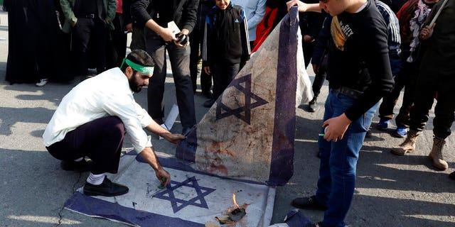 Protesters burn representations of Israeli flag during a demonstration over the U.S. airstrike in Iraq that killed Iranian Revolutionary Guard Gen. Qassem Soleimani, in Tehran, Iran, Jan. 3, 2020. Iran has vowed