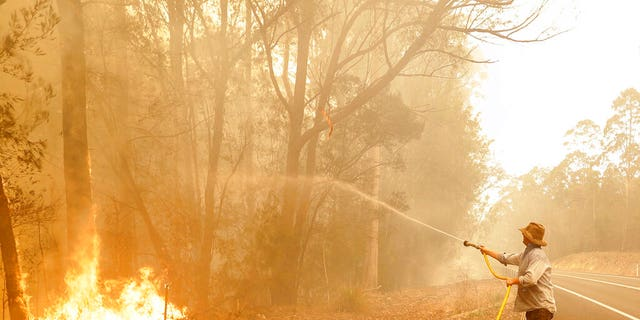A man uses a water hose to battle a fire near Moruya, Australia, Saturday, Jan. 4, 2020. Australia's Prime Minister Scott Morrison called up about 3,000 reservists as the threat of wildfires escalated Saturday in at least three states with two more deaths, and strong winds and high temperatures were forecast to bring flames to populated areas including the suburbs of Sydney.