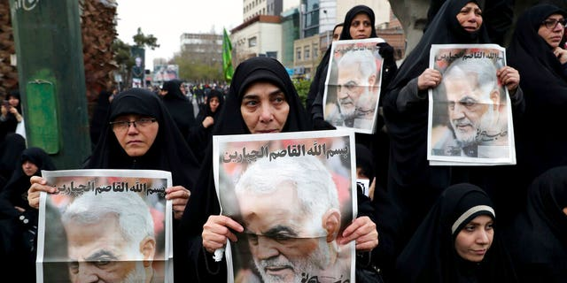 "Protesters hold up posters of Gen. Qassem Soleimani while mourning during a demonstration over the U.S. airstrike in Iraq that killed Iranian Revolutionary Guard Gen. Qassem Soleimani, in Tehran, Iran, Saturday Jan. 4, 2020. Iran has vowed ""harsh retaliation"" for the U.S. airstrike near Baghdad's airport that killed Tehran's top general and the architect of its interventions across the Middle East, as tensions soared in the wake of the targeted killing. (AP Photo/Ebrahim Noroozi)"