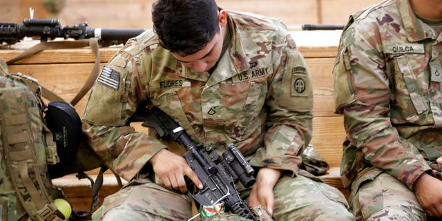 A U.S. Army soldier checking his rifle before heading out Saturday at Fort Bragg, N.C., as troops from the 82nd Airborne were deployed to the Middle East. (AP Photo/Chris Seward)