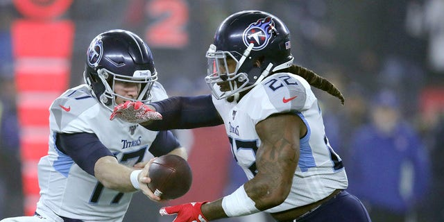 Tennessee Titans quarterback Ryan Tannehill, left, hands off to running back Derrick Henry in the first half of an NFL wild-card playoff football game against the New England Patriots, Saturday, Jan. 4, 2020, in Foxborough, Mass. (Associated Press)