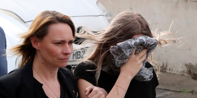 A 19-year-old British woman, right, that was found guilty of making up claims she was raped by up to 12 Israelis, arrives at Famagusta District Court with her mother for sentencing on Tuesday, Jan. 7, 2020. A Cyprus court handed a four-month suspended sentence to a 19-year-old British woman who was found guilty of public mischief for making up claims that she was raped by up to a dozen Israelis. (AP Photo/Petros Karadjias)