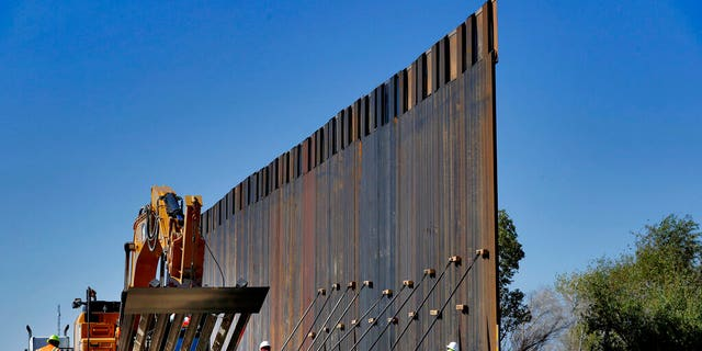 FILE: Government contractors erect a section of Pentagon-funded border wall along the Colorado River in Yuma, Ariz.