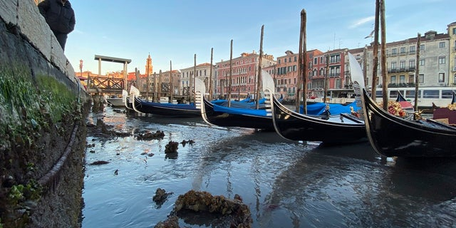 Gondolas are stranded in Venice, northern Italy, during exceptionally low tide.  (AP Photo/Luigi Costantini)