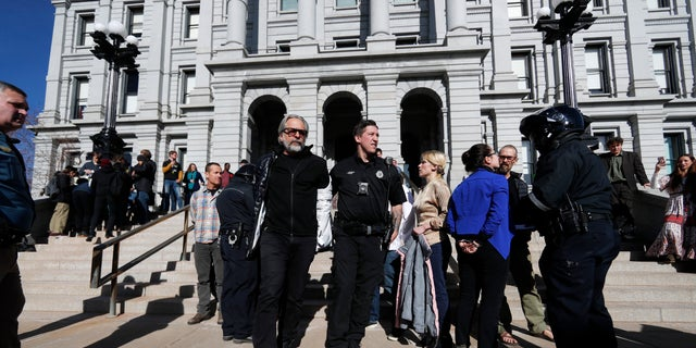 A Denver Police Department officer leads away one of several anti-fracking protesters who interrupted the State of State speech by Colorado Gov. Jared Polis in the State Capitol Thursday, Jan. 9, 2020, in Denver. (AP Photo/David Zalubowski)